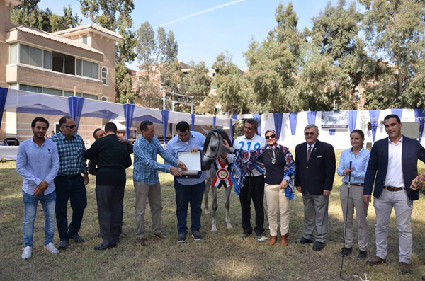 Heba El Bourini admires her award with her delighted owner/breeder, Mr. Mohamed El Bourini and his family and friends, during the WAHO Trophy presentation by Peter Pond, WAHO President.